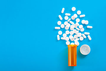 Aerial shot of white pills spilling out of a prescription bottle onto a blue background