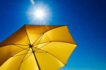 Bright sun shines down from a deep blue sky, shielded by a large yellow beach umbrella