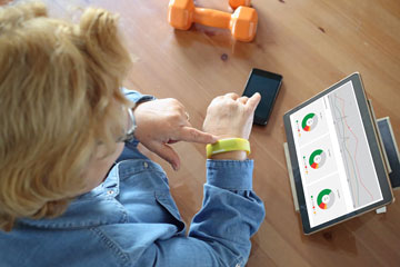 Older woman using fitness band, with feedback displayed as graphics on a tablet computer