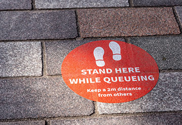 Sticker on the pavement which reads 'Stand here while queueing. Keep a 2 metre distance from others'