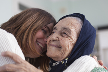 A woman hugs a grey-haired woman wearing a headscarf. Both are smiling.