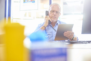 Concerned GP on the telephone, looking at a discharge summary on a tablet